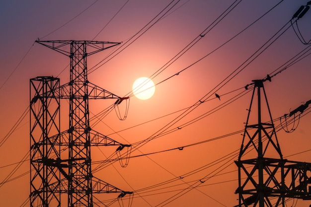 High voltage steel transmission tower during sunset