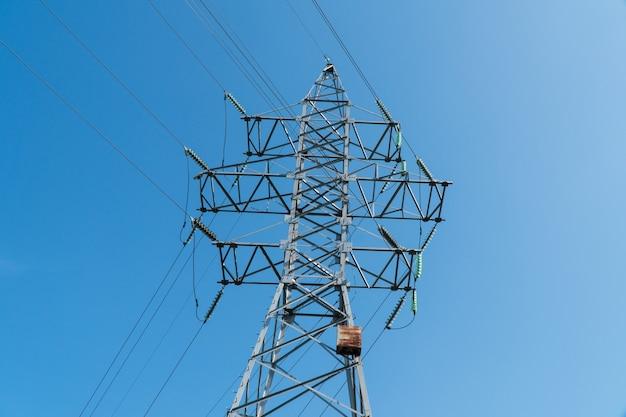 Башня высокого напряжения против голубого неба Premium Фотографии