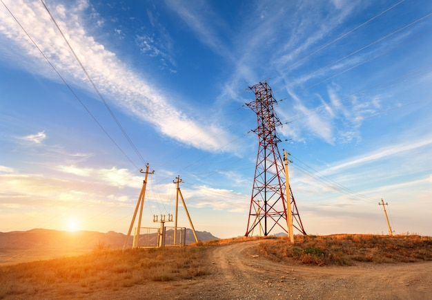 Башня высокого напряжения в горах на закате. электричество пилон