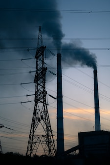 Фон неба высоковольтной башни, заводская труба с дымом над ней