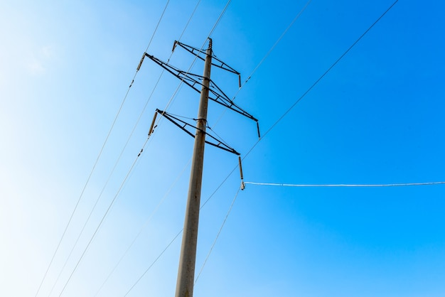 High-voltage transmission line with concrete supports, blue sky. electrical system