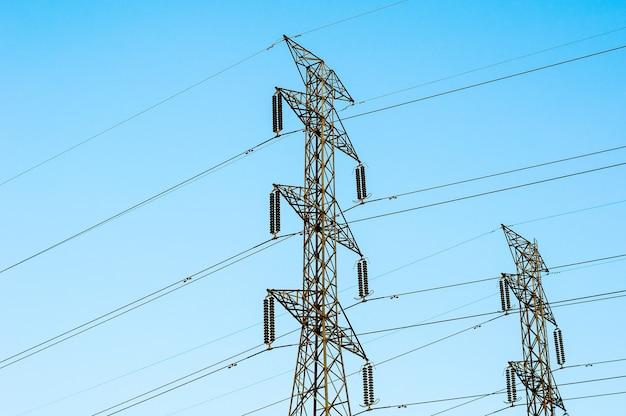 Высокое напряжение линий передачи, изолированных на фоне голубого неба