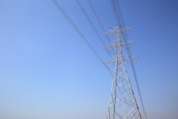 Башня высоковольтной передачи и проводка электрического напряжения на голубом небе