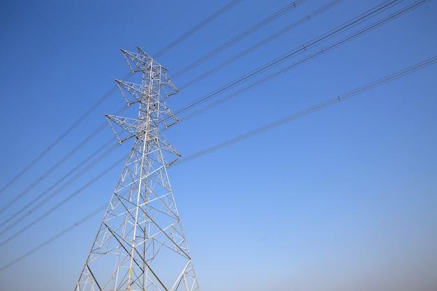 Башня передачи высокого напряжения и кабель электропроводки напряжения тока с предпосылкой неба.