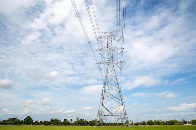 Башня передачи высокого напряжения и проводка кабеля с предпосылкой неба.