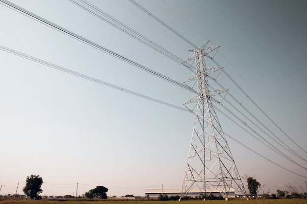High-voltage transmission tower and electricity voltage wiring cable with sky background.