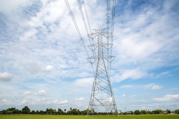 High-voltage transmission tower and wiring cable with sky background.