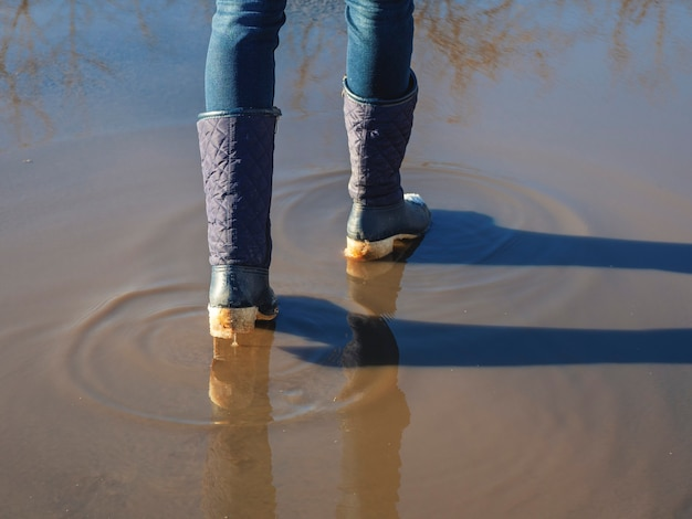 High water, the ice melts in the spring, a woman walks through puddles on the street, spring weather.