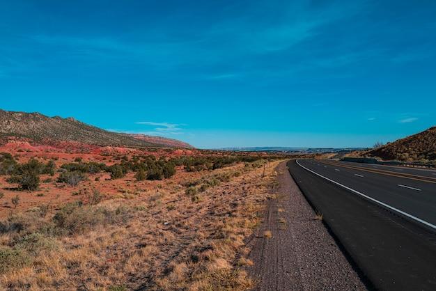 夏の青空と暑い晴れた日に極度の熱かすみでアメリカ南西部の不毛の風景を走る高速道路。