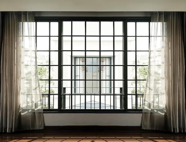 Интерьер с высокими окнами и занавесками с солнечным светом снаружи в гостиную