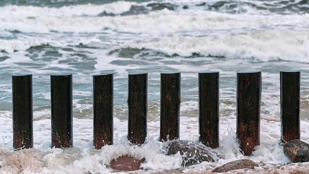 Высокие деревянные волнорезы в голубых брызгах морских волн, вид крупным планом. длинные шесты или борозды в воде