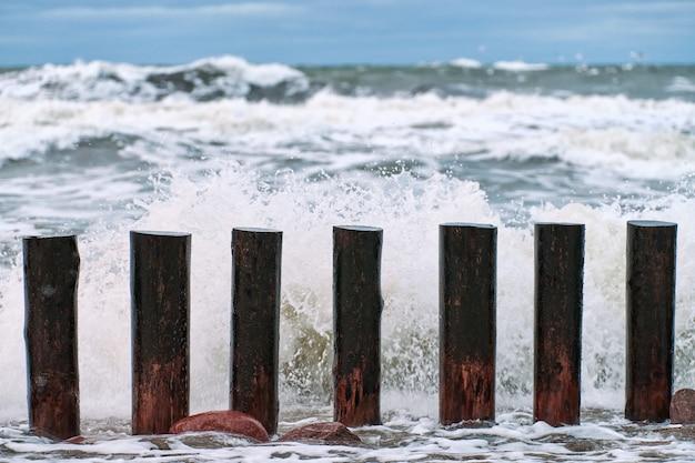 Высокие деревянные волнорезы в плещущихся морских волнах, красивое облачное небо, вид крупным планом