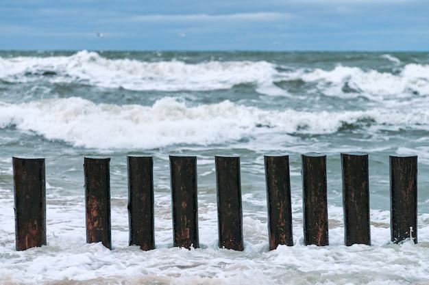 High wooden breakwaters in splashing sea waves, beautiful cloudy sky, close up view