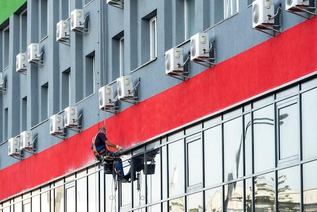 Высотные работы на современном здании с альпинизмом