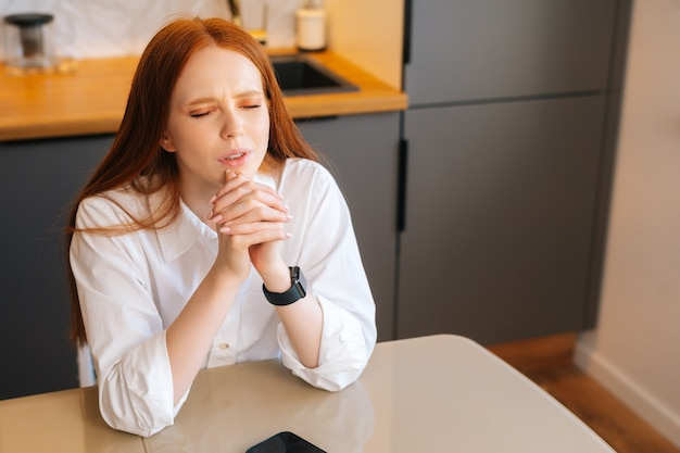 Highangle view of sad young woman praying with eyes closed holding folded hands in front of face at