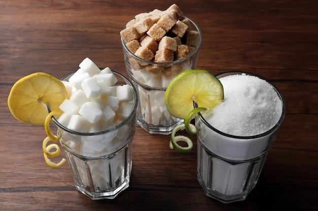 Стаканы хайбол с гранулированным и кусковым сахаром на деревянном столе
