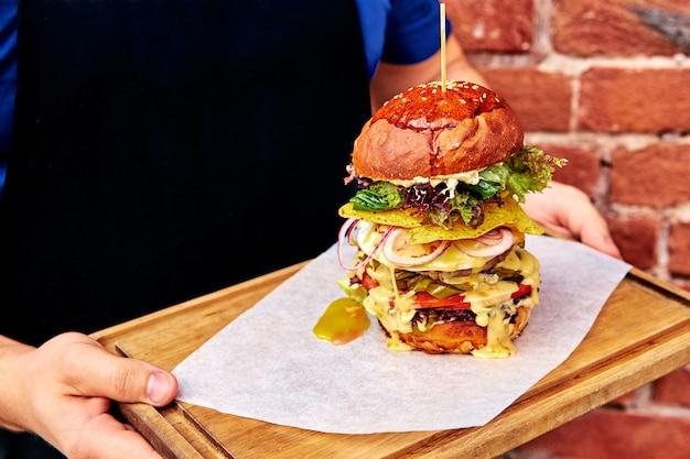 Бургер на подносе в руках