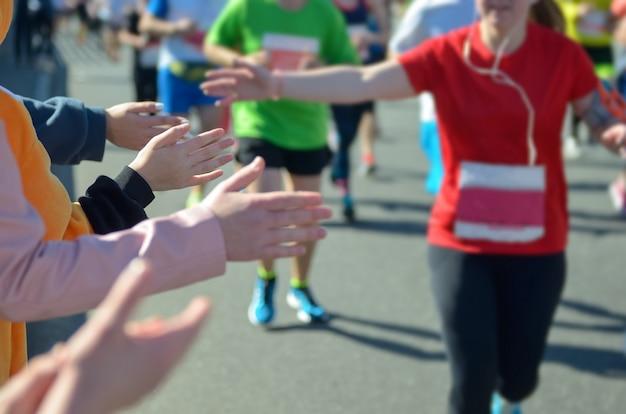 Марафонский забег, поддержка бегунов на дороге, рука ребенка раздает highfive