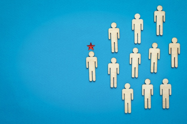 The highlighted leader among a group of little men on a blue background. the concept of the head. business idea.