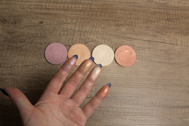 Highlighter swatches on a female hand on a wood background closeup