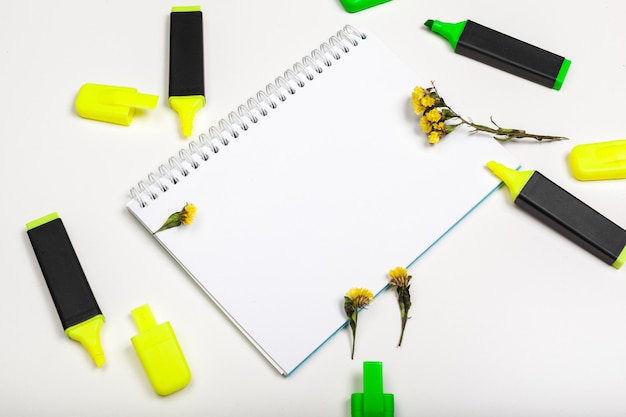 Highlighters and  blank notepad paper sheet flat lay on a desk