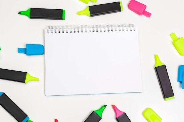 Highlighters and  blank notepad paper sheet