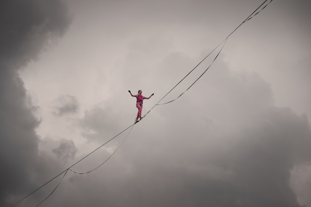 Highliner girl on the background of the cloudy sky