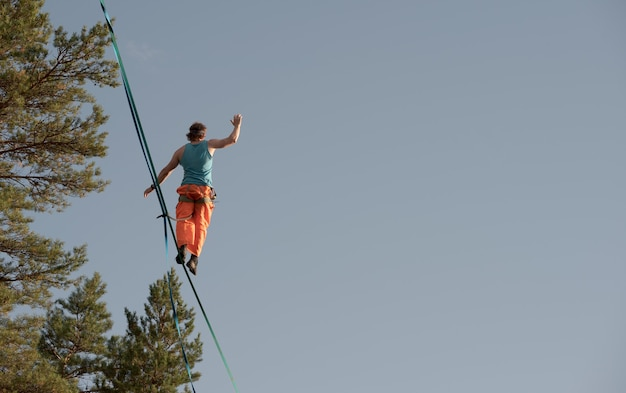 Highliner walks on a tightrope against the backdrop of the sky