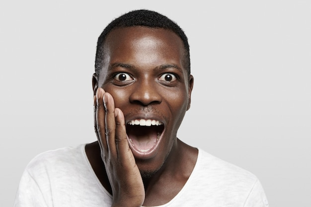 Highly-detailed close up portrait of excited african male in white t-shirt, looking surprised, screaming in shock with mouth wide open, holding hand on cheek, astonished with some unbelievable story