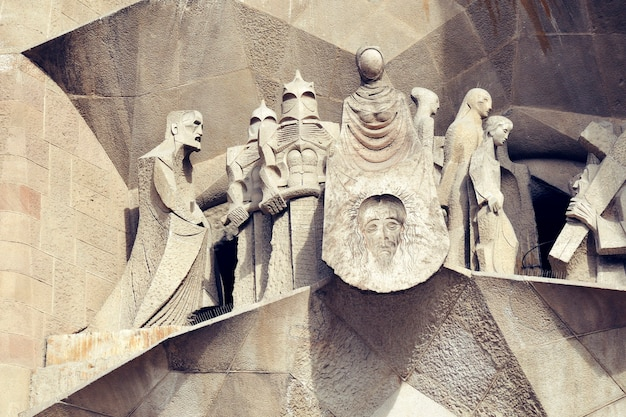Детализированные скульптуры над входом в страстный фасад знаменитой достопримечательности барселоны - храма саграда фамилия.