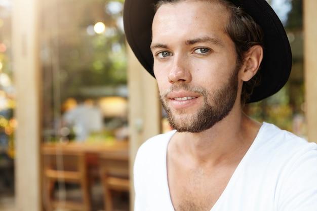 공정한 머리와 트렌디 한 모자를 쓰고 포장 카페에서 포즈 분명 그을린 피부와 매력적이고 세련된 젊은 수염 파란 눈 남성 모델의 매우 상세한 샷