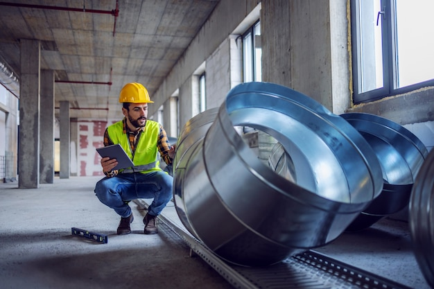 Highly motivated caucasian construction worker in work wear crouching next to exhaust pipes and checking on their quality. in hands is tablet.