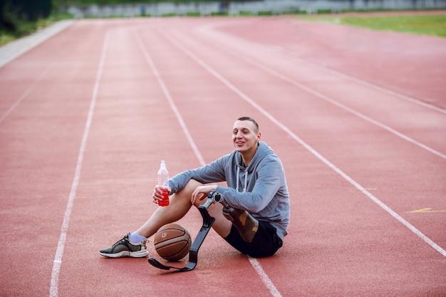 競馬場の上に座って、リフレッシュメントを保持しているスポーツウェアで非常にやる気のあるハンサムな白人スポーティな障害を持つ男。足の間はバスケットボールです。