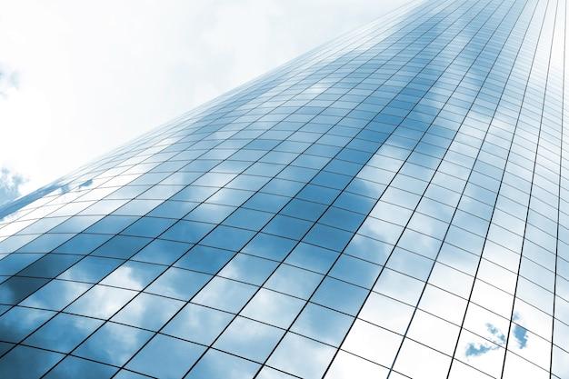 Высотное стеклянное здание с отражением облаков и скз
