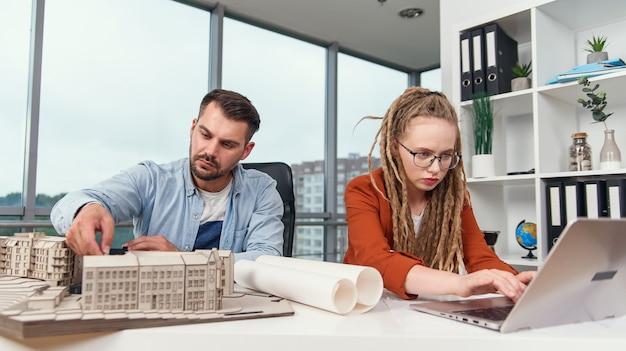 미래 건물의 모형으로 작업하는 고도로 숙련 된 열심히 일하는 창의적인 남녀 디자이너