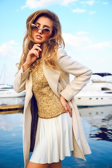 カールしたトレンディなオンブルヘア、居心地の良い秋のクリームウールコート、ゴールデントップとサングラス、畏敬の念ポートとヨットクラブの素晴らしいwhewの美しいモデルのファッション性の高い肖像画。