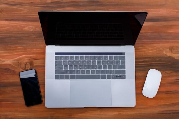 뚜껑이 열린 하이테크 플랫 은색 고급 노트북 컴퓨터는 나무 배경에 격리된 상태로 표시됩니다. 상위 뷰 샷입니다.