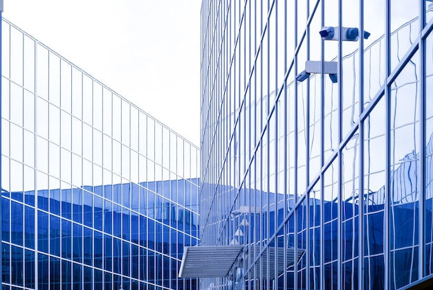 Hightech style cityscape fragment of glass and metal building facades with surveillance cameras