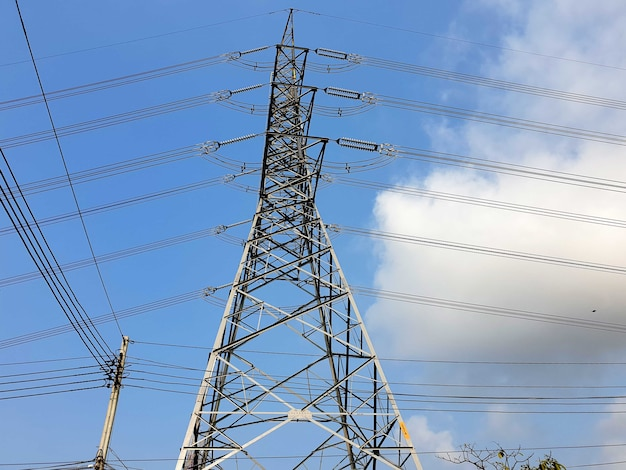 Highvoltage electrical transmission tower on clouds in blue sky background