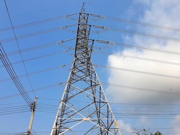 Башня электропередачи высокого напряжения на облаках на фоне голубого неба