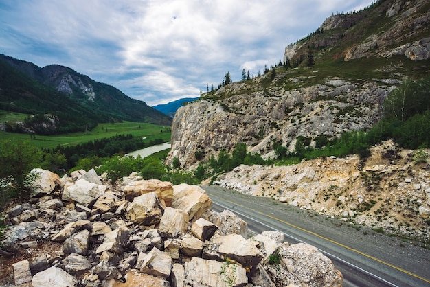 Highway across pass in mountains. asphalt road near rocky cliff. mountain river in valley.
