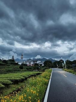 Шоссе среди полей под темными облаками