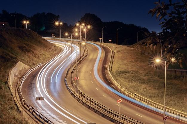 야간 조명에 고속도로입니다. 교환 다리 도로의 빠른 자동차 빛 경로, 산책로 및 줄무늬. 야간 조명 그림 줄무늬. 장노출 촬영