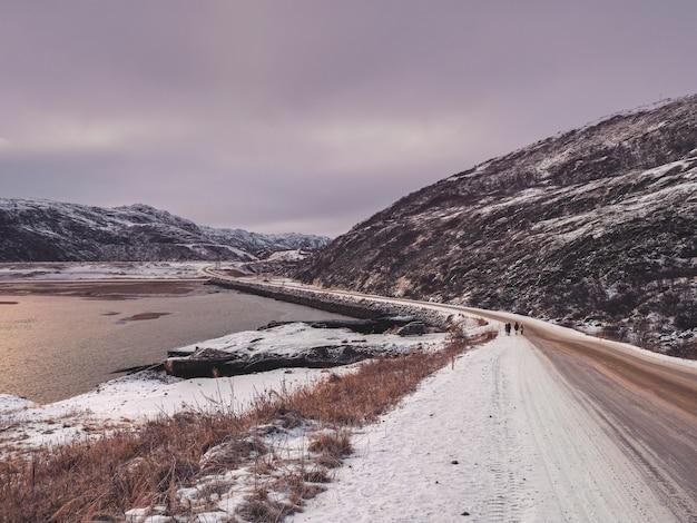 北極の丘の間の高速道路。北の冬の道、道を曲がる