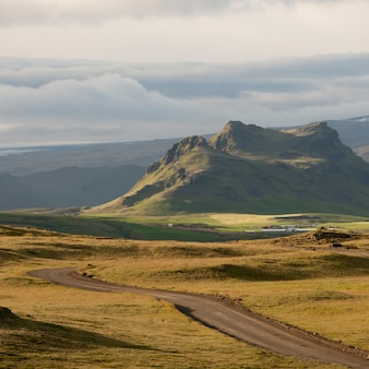 Highway disappearing towards mountains through grasslands of iceland