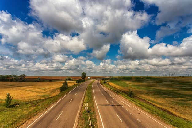 Highway from the height of the bridge, against the background of clouds, fields and blue sky