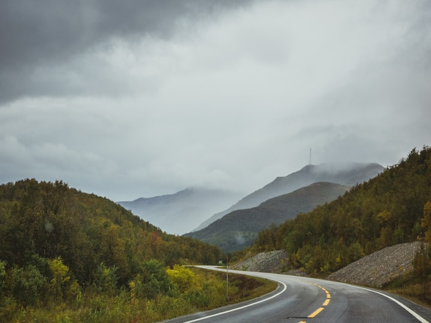 Highway near the forest in the mountains under the dark cloudy sky