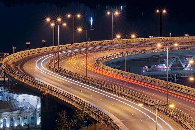 Highway at night lights. fast car light path, trails and streaks on interchange bridge road. night light painting stripes.