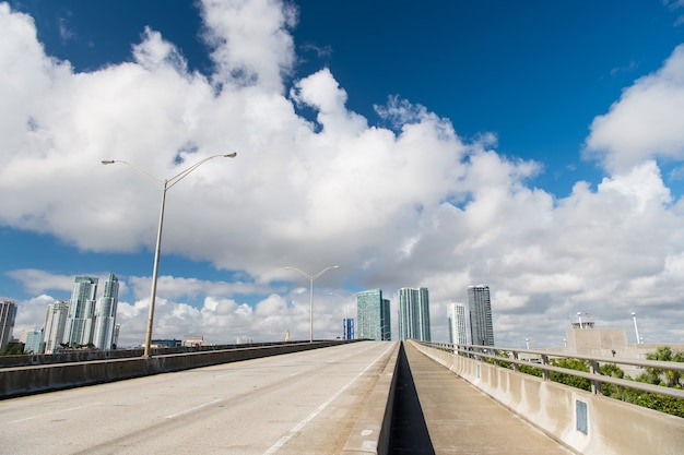Highway or public road roadway for transport vehicles and urban skyscrapers on cloudy blue sky backgroun