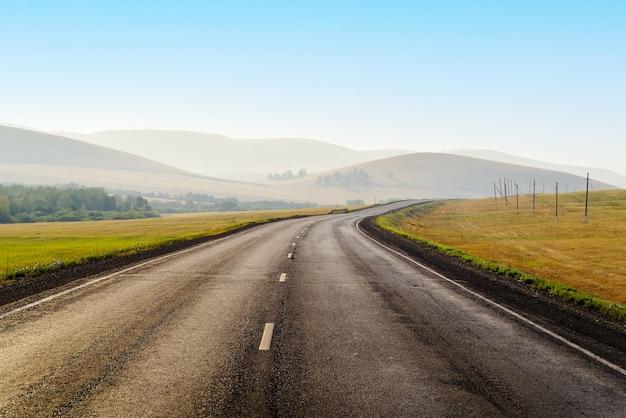 早朝に丘の間の距離に伸びる高速道路写真はロシアで撮影されました